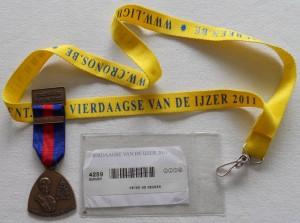 de badge met barcode die ik aan de controleposten moest tonen en de medaille die ik als beloning kreeg voor het succesvol beëindigen van de opdracht.